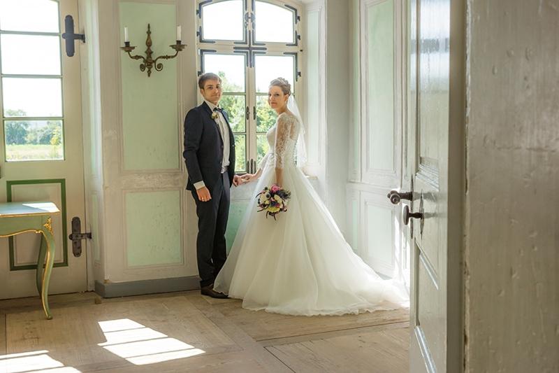 Ein Brautpaar im Schloss vor einem Fenster