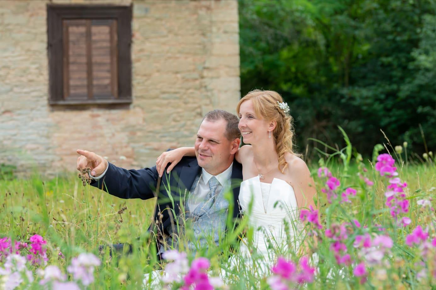 Brautpaar in der Wiese hinter Blumen